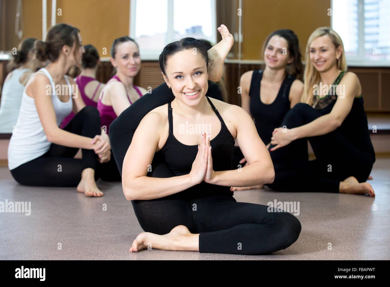 Smiling yogi girl in class in Yoga asana, exercising, stretching - Stock Image