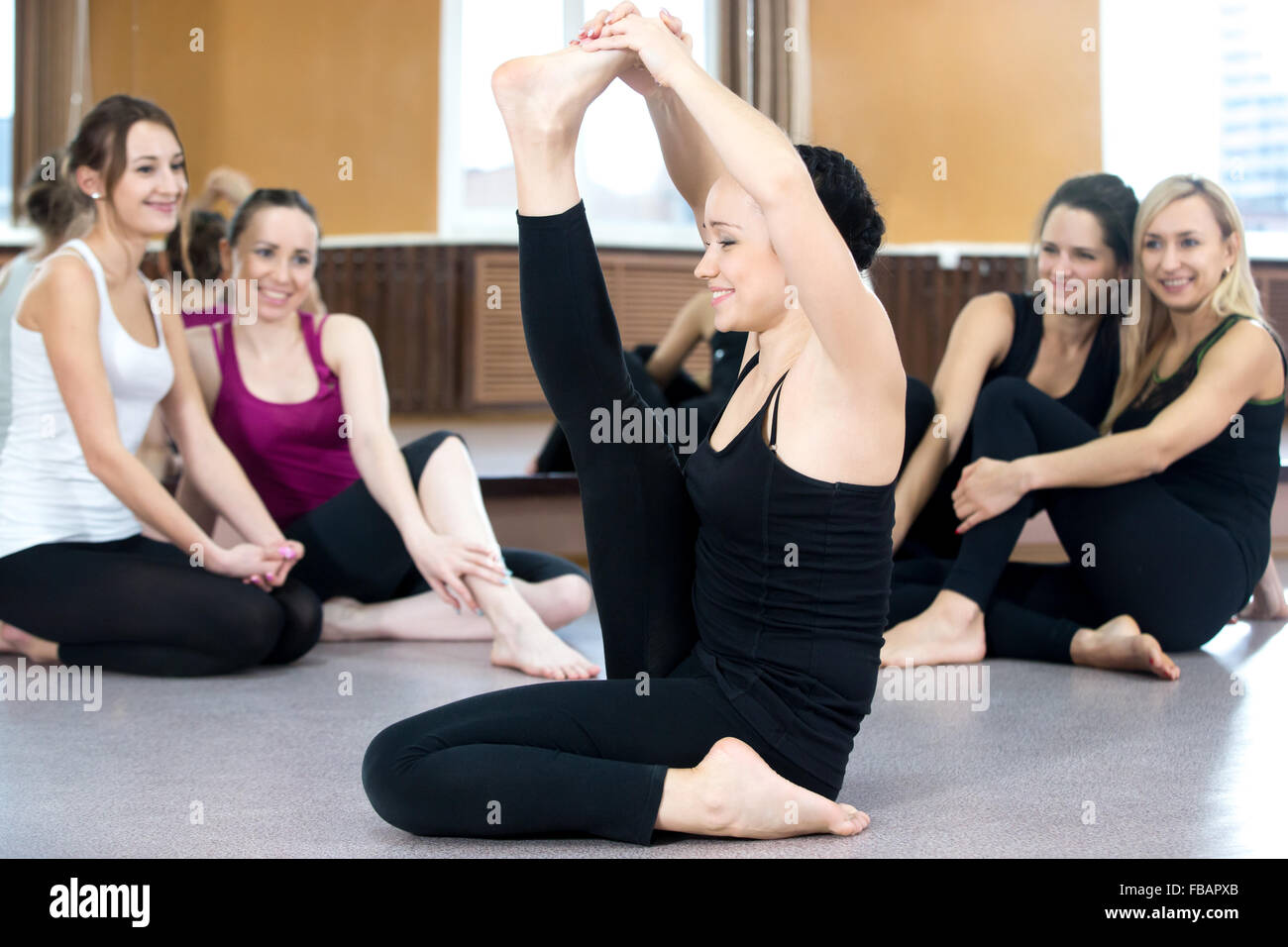 Yoga girl practices stretching, doing fitness exercises in black sportswear in class, group of friends watching - Stock Image