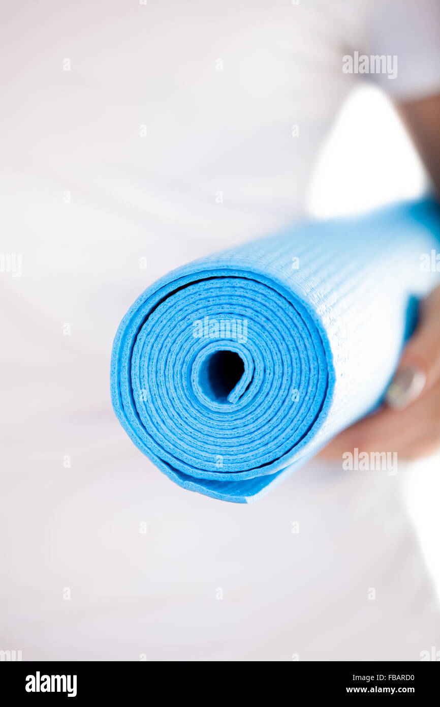 Close up, white woman hands holding folded blue yoga, pilates mat, ready for fitness exercises. Healthy life, keep - Stock Image