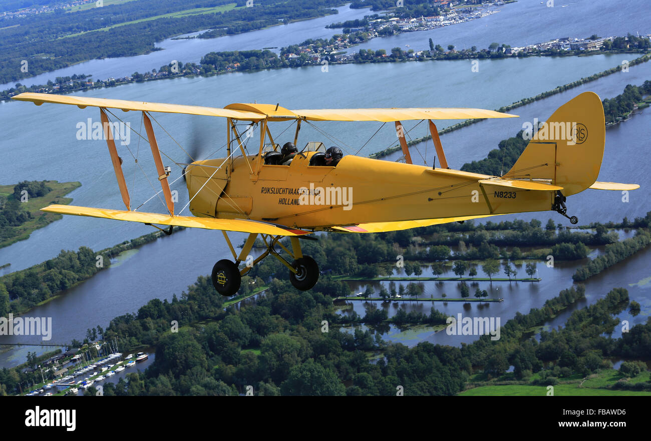 A de Havilland Tiger Moth bi-plane over the Dutch countryside - Stock Image