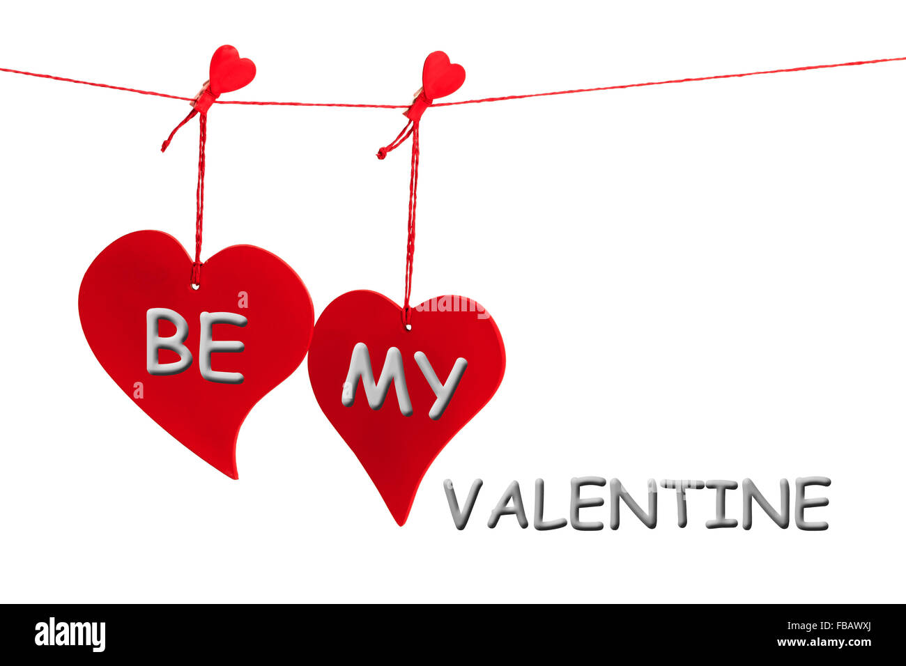 Two hanging red hearts with BE MY VALENTINE text in grey isolated on white background - Stock Image