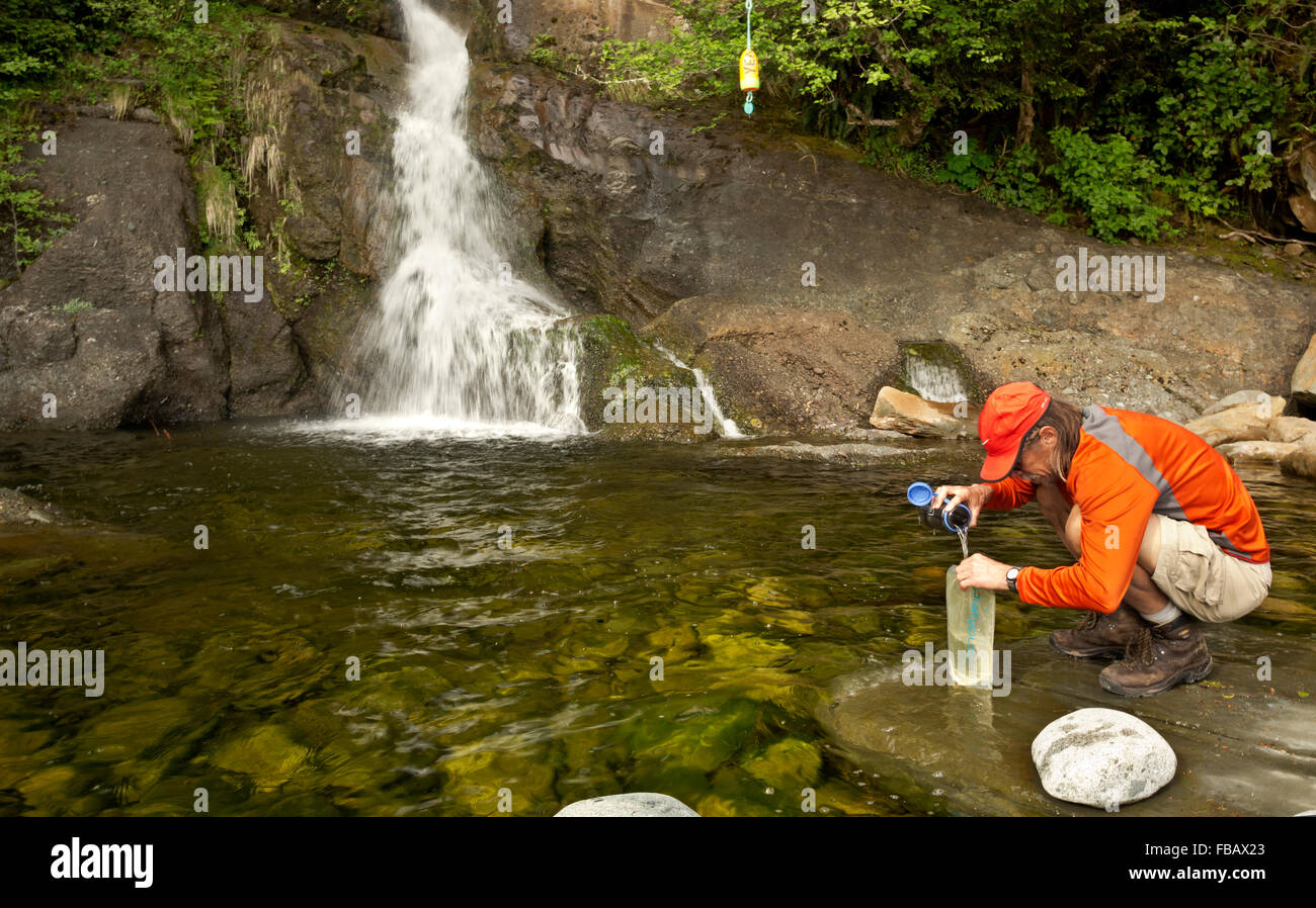 BRITISH COLUMBIA - Hiker filling water bottles at the base of Tsocowis Creek Falls along West Coast Trail at Tsocowis - Stock Image