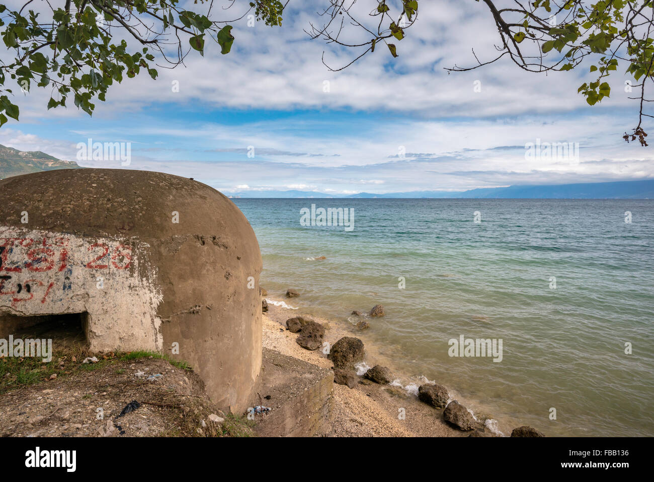 Bunker built under communist dictator Hoxha at Lake Ohrid, Macedonian shore in distance, near Pogradec, Albania - Stock Image