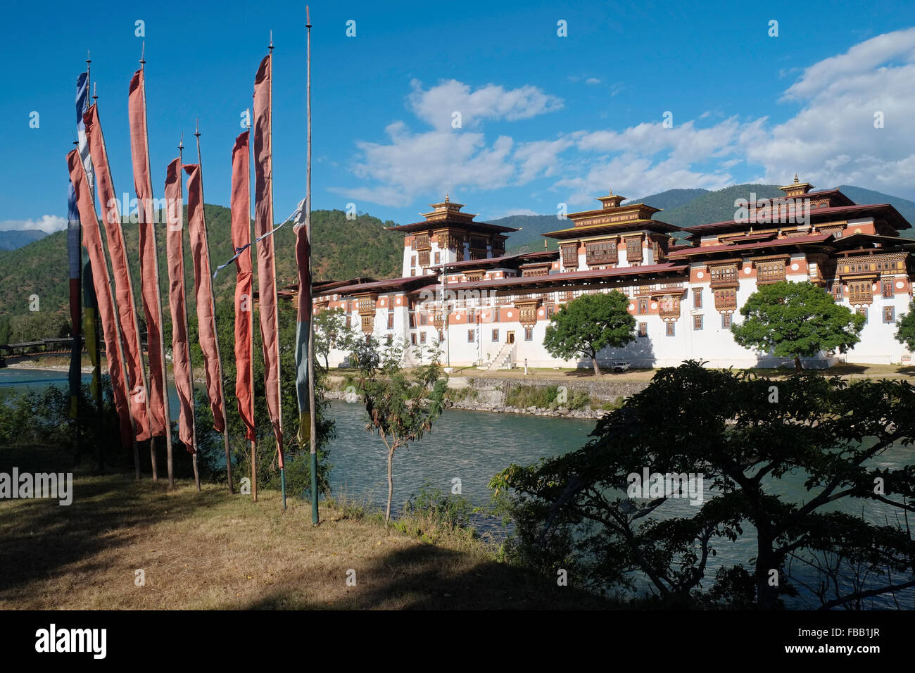 Buddhist prayer flags facing the Punakha Dzong (also known as Pungtang Dechen Photrang Dzong), Punakha, Bhutan. - Stock Image