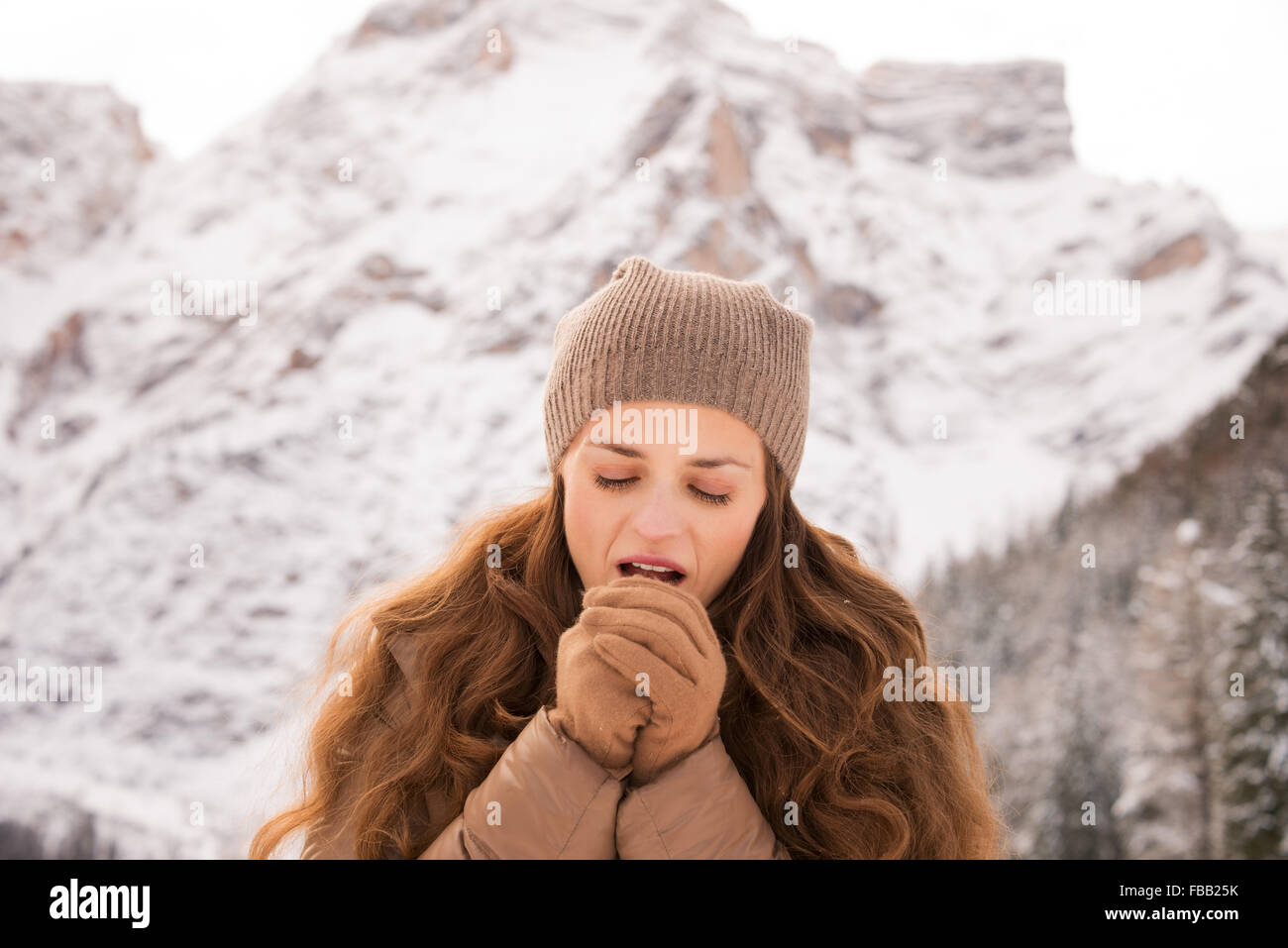 Energy-filling and exciting winter weekends in the mountains. Portrait of young woman warming hands with breathe - Stock Image