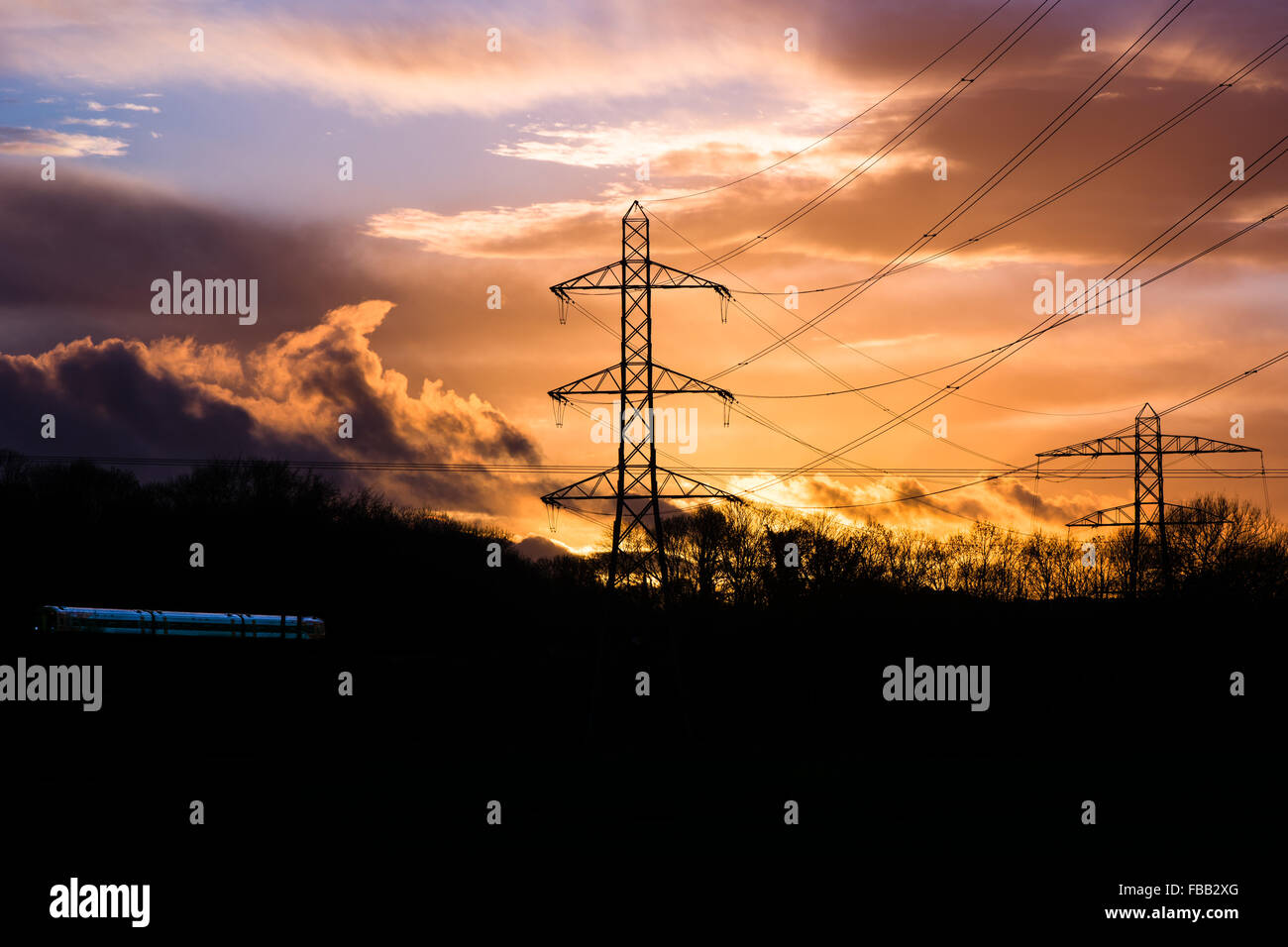 Industrial landscape with cables, train and sunset. Electricity cables and pylons are silhouetted in front of a - Stock Image
