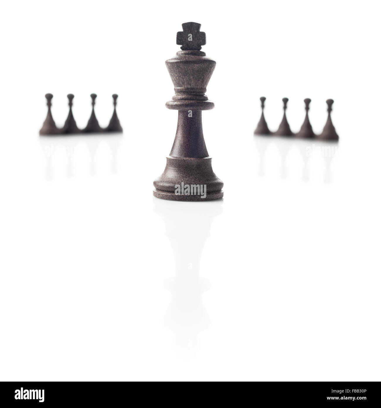 Chess. Black king, eight pawns out of focus and their shadows on white background. Power, competition or leadership - Stock Image