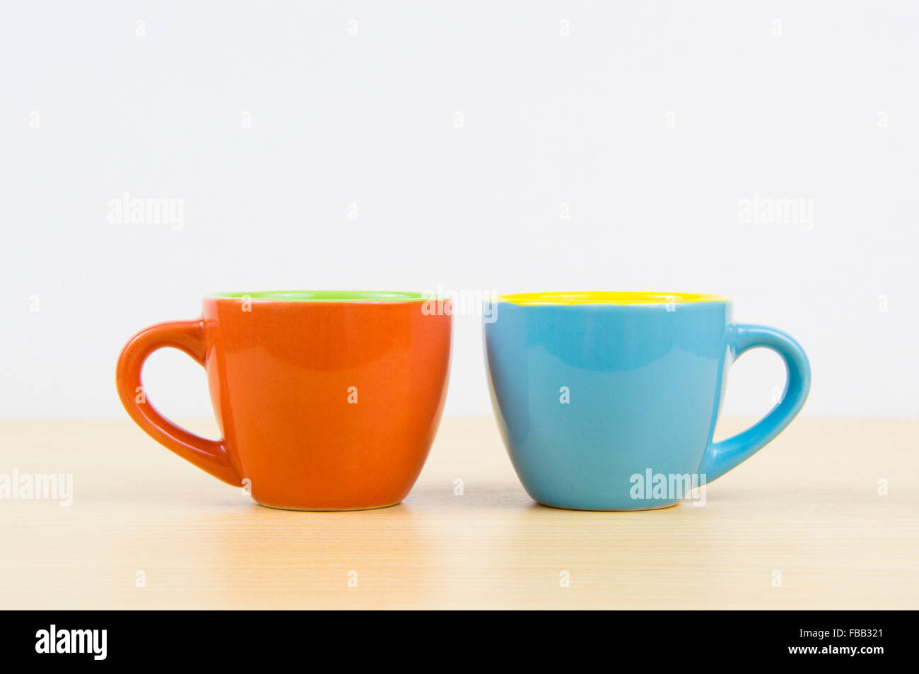 colorful coffee cups on wood board and white background stock photo