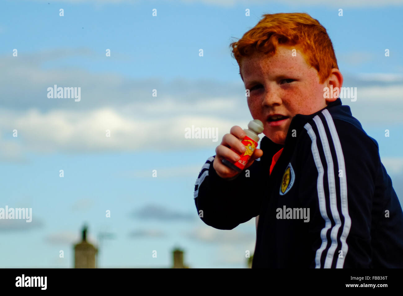 A young Scottish boy with red hair enjoys a candy on the beach in Lossiemouth, Scotland. - Stock Image