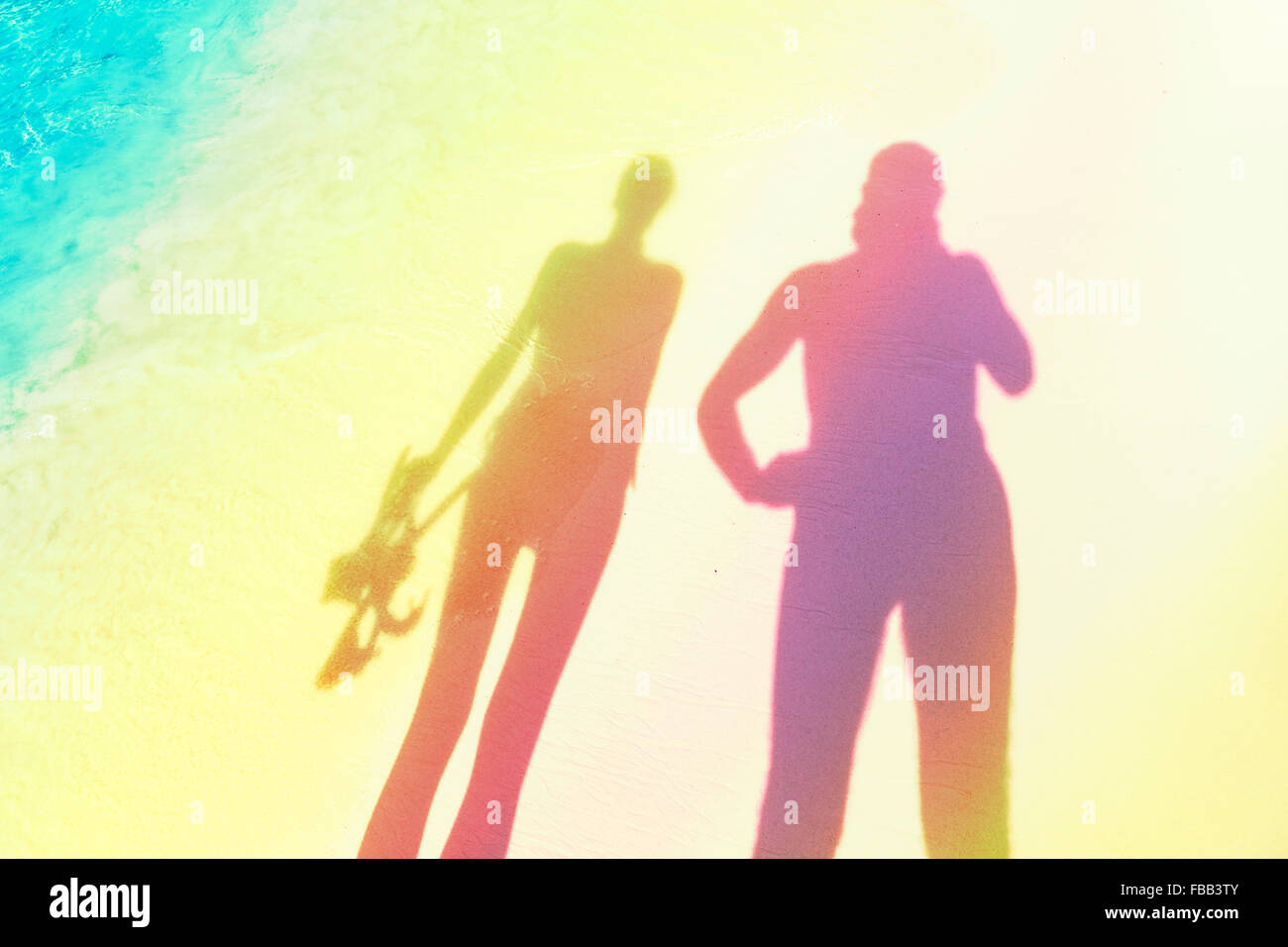 Stylized silhouettes of woman holding snorkeling equipment and man on the beach. - Stock Image