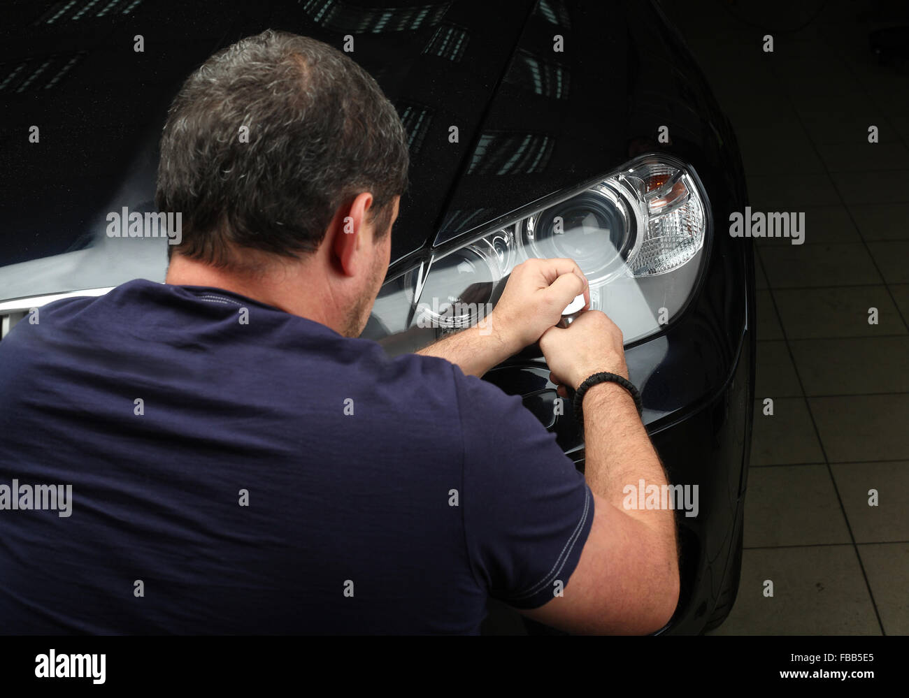 The worker polishes optics of headlights of the car with the electric tool. Close up - Stock Image