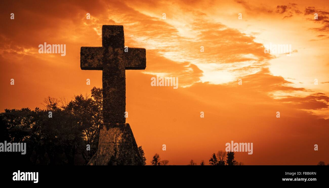 Judgement Day. Stone cross set against a blood red sky. - Stock Image