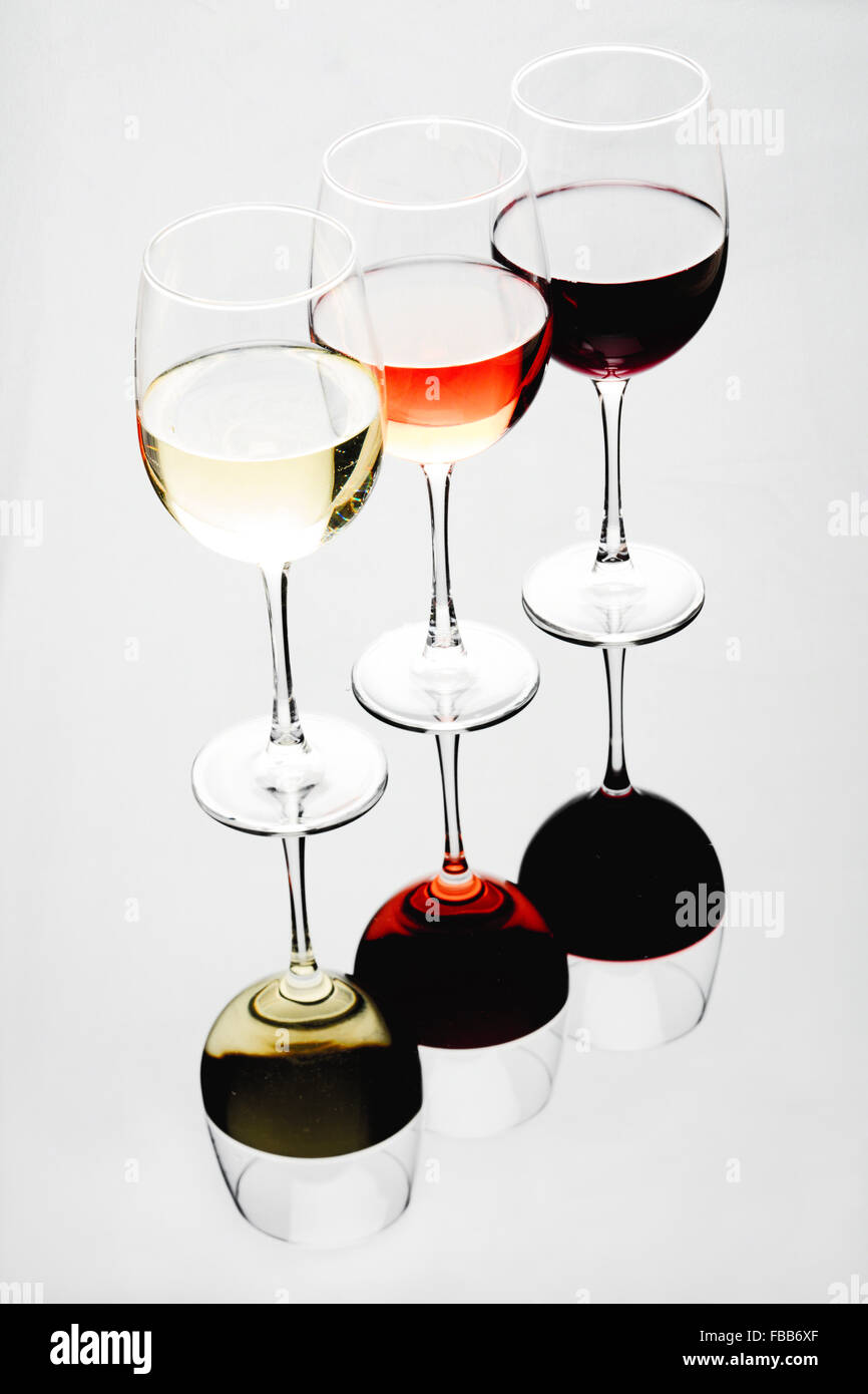 Three Glasses Filled with White, Rose and Red Wines on an Illuminated Background with Reflections - Stock Image