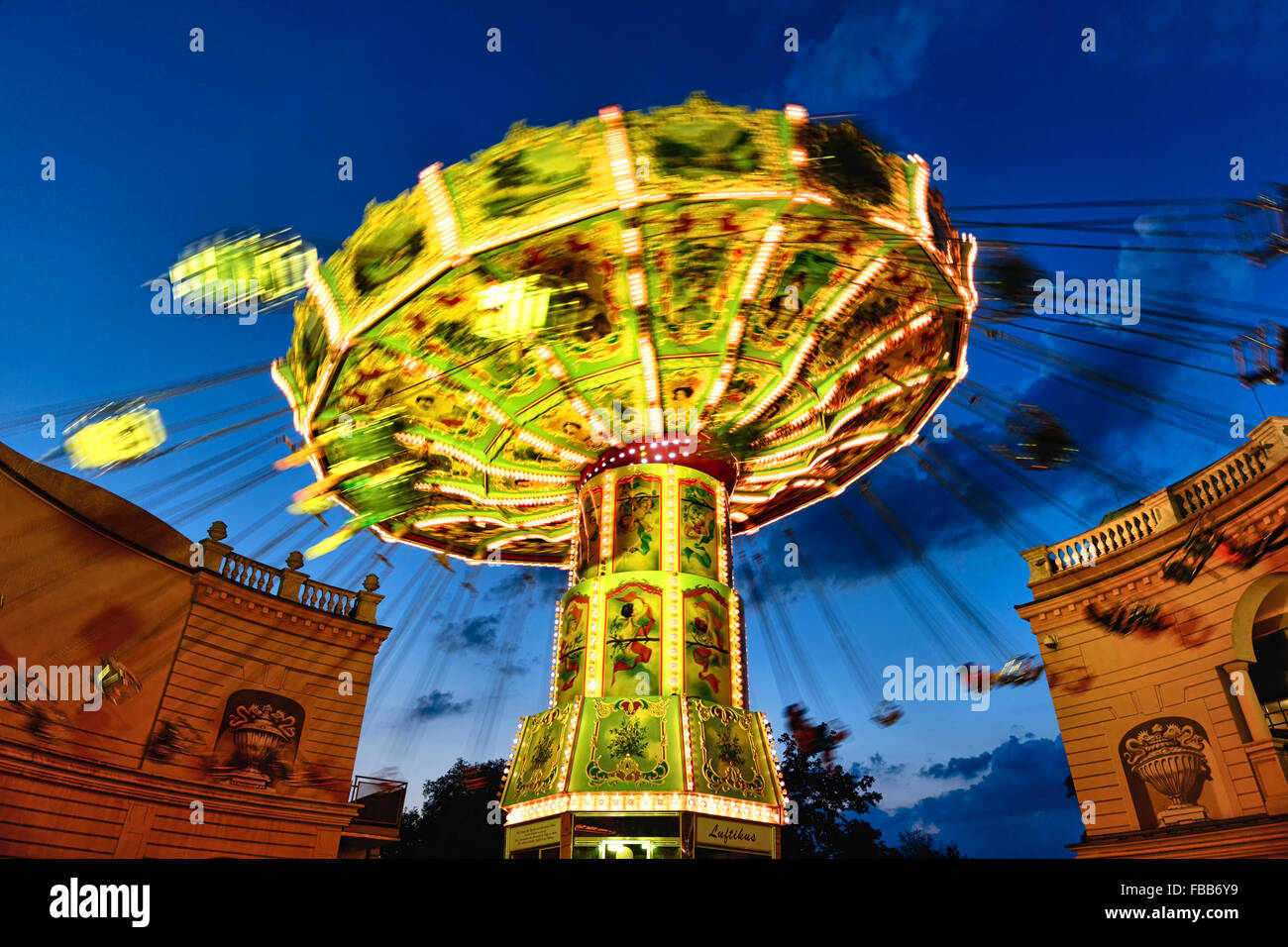 Low Angle View of a Moving Chain Swing Ride at Dusk, Prater Amusement Park, Vienna, Austria - Stock Image
