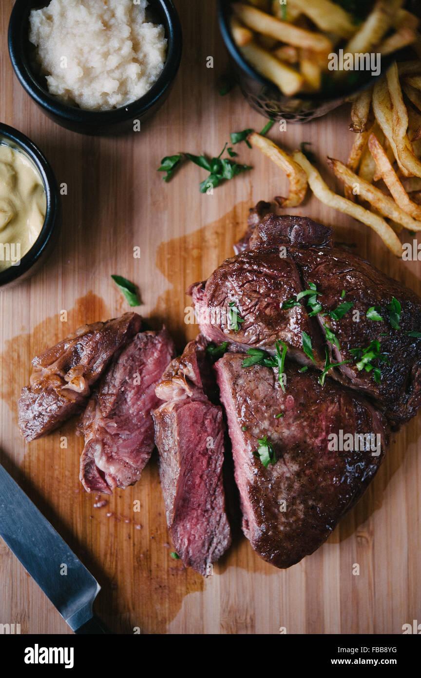 Sliced Angus Ribeye Steak with Fries, Mustard and Horseradish - Stock Image