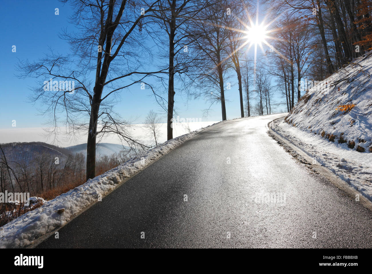 Empty road in winter with sun beam in the sky - Stock Image