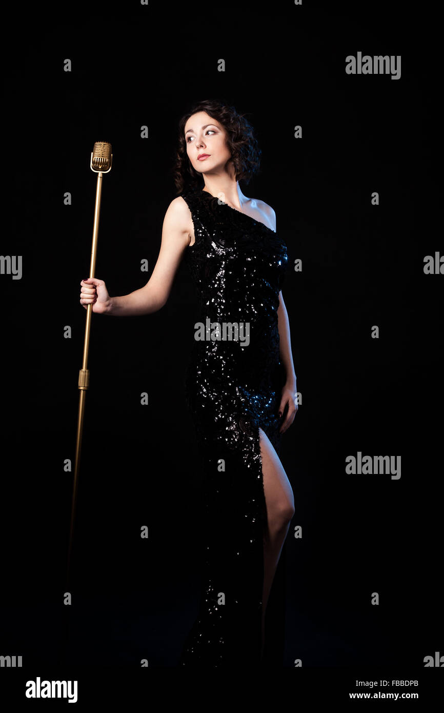 Beautiful young female vocalist in shiny black evening dress prepare to sing during musical show, excitement, emotions - Stock Image