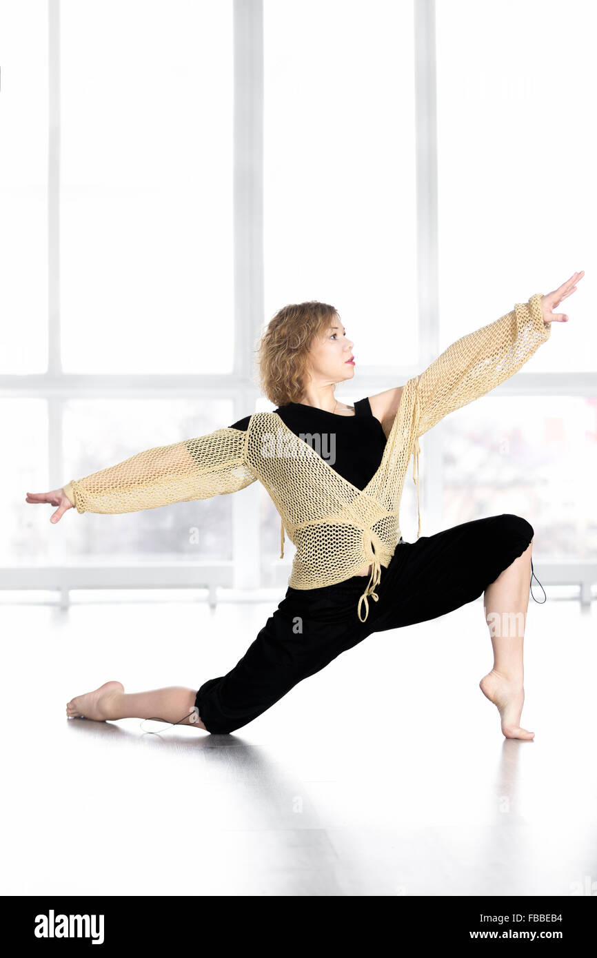 Sporty dancer woman in class dancing, doing aerobics training, fitness choreography zumba, balancing in lunge - Stock Image