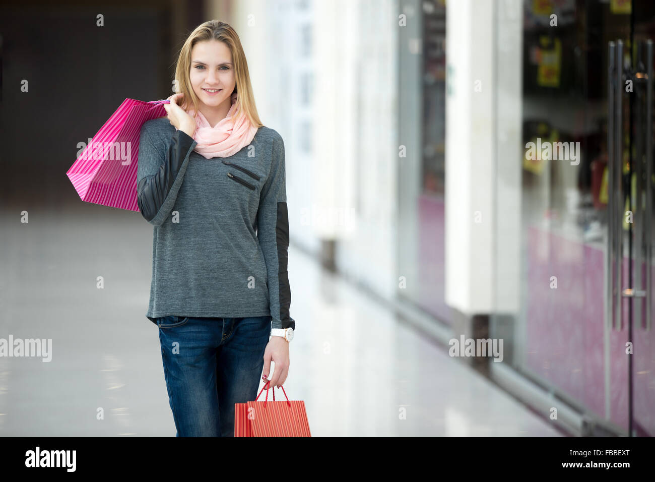 Smiling beautiful teenage girl walking in shopping center with colorful paper bags, passing shopwindow with discount - Stock Image