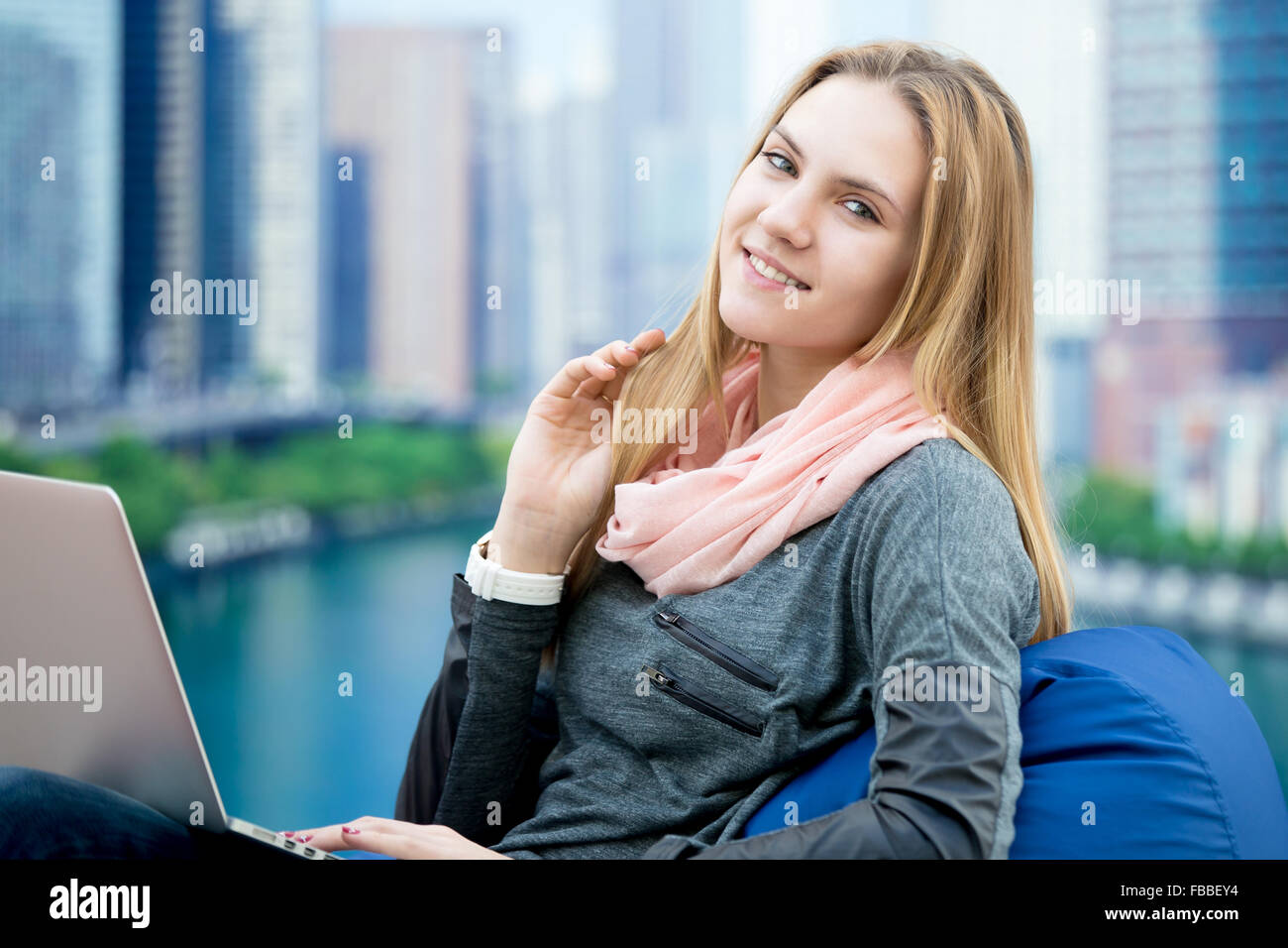 Happy smiling girl sitting in comfortable bean bag chair with her portable computer, big city on the background - Stock Image