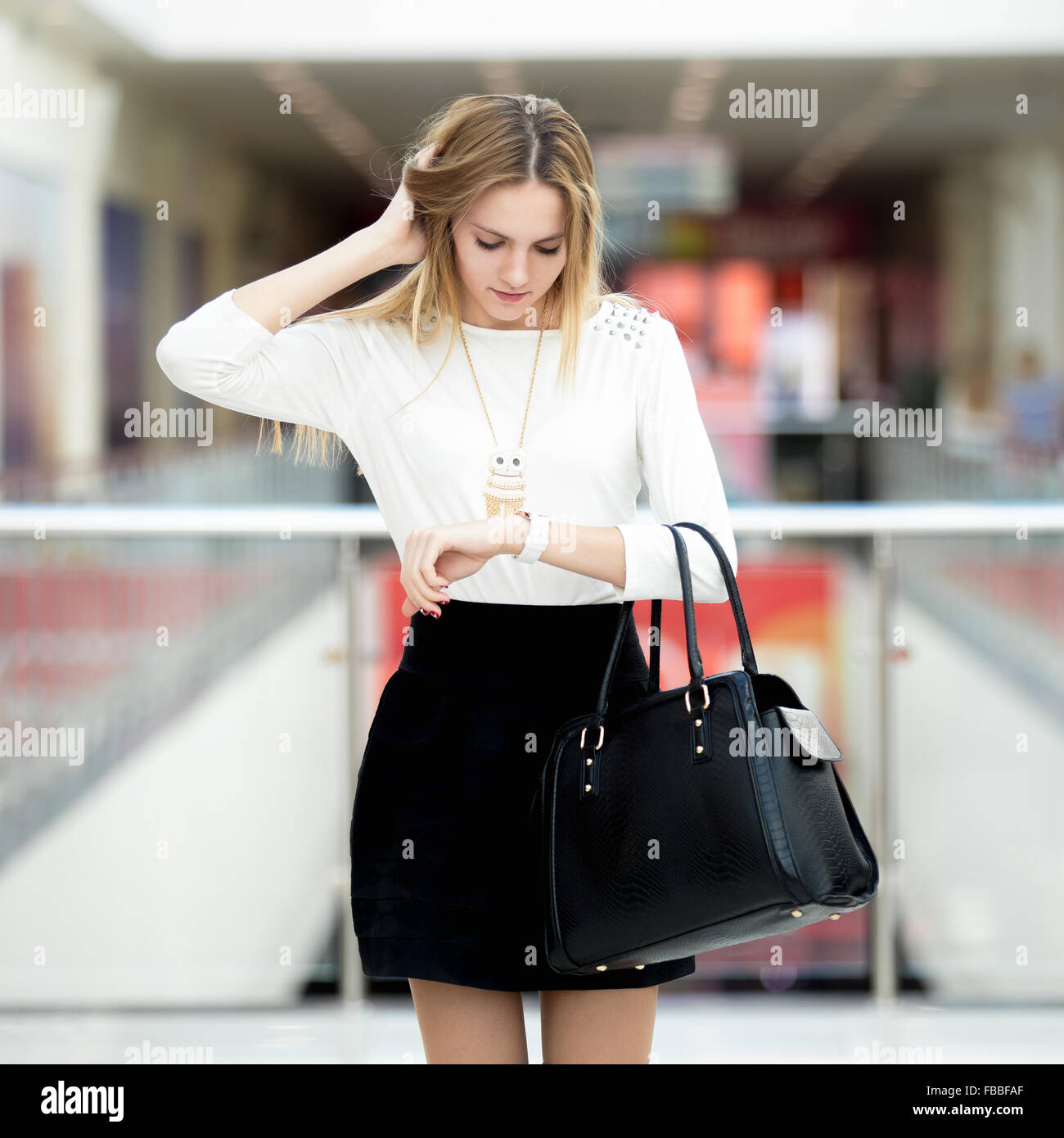 Young business woman in fashionable outfit, holding her head in dismay, running late for meeting, hurrying, waiting, - Stock Image
