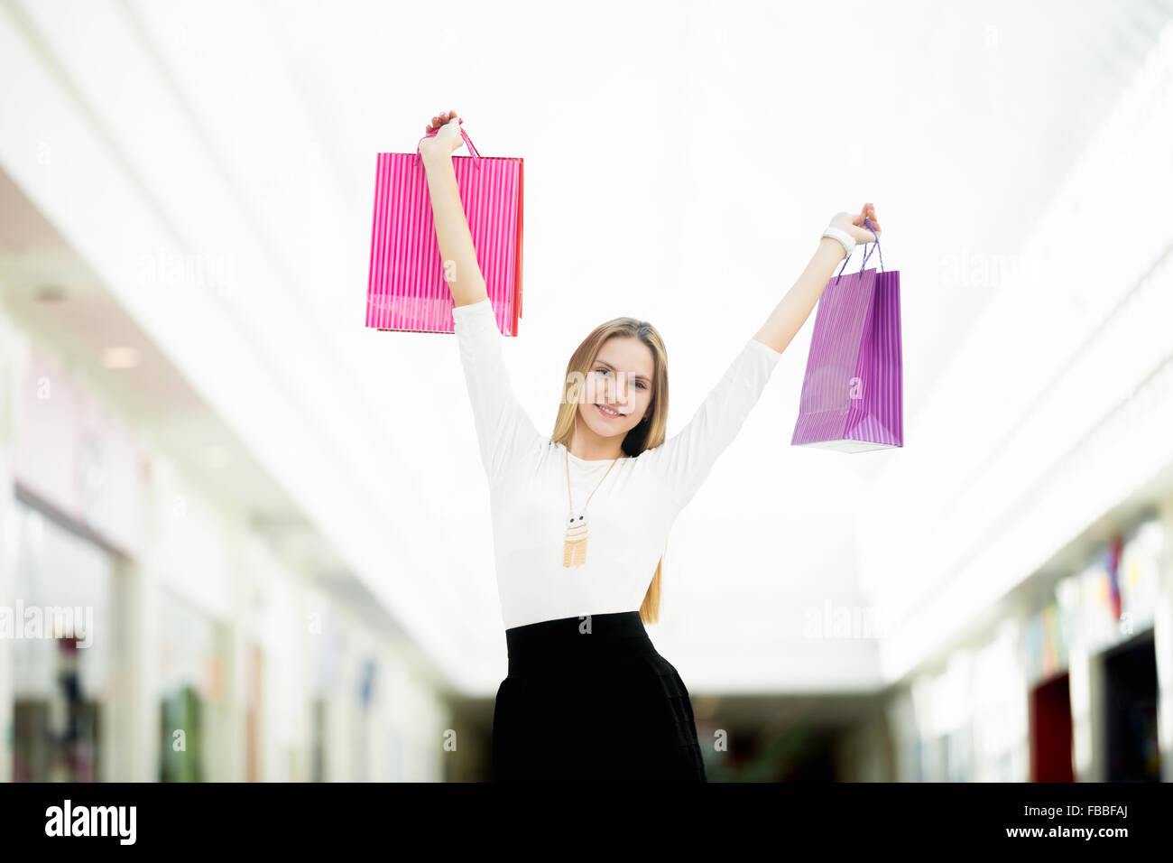 Cheerful young woman happy with her purchases, dancing with shopping bags. Sale, discount, fashion, profitable offer - Stock Image