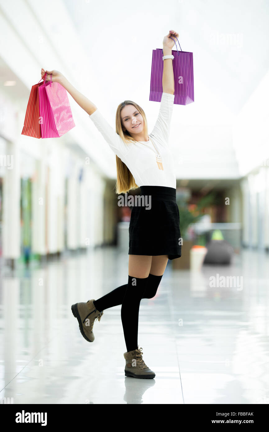 Playful young woman dancing with shopping bags happy and excited. Sale, discount, fashion, profitable offer concepts - Stock Image