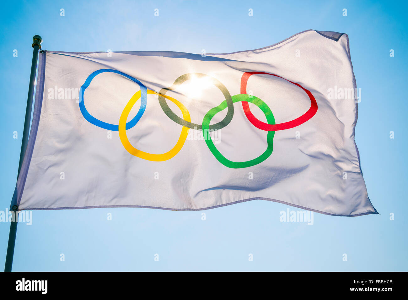 RIO DE JANEIRO, BRAZIL - FEBRUARY 12, 2015: An Olympic flag flutters in the wind backlit against bright blue sky. - Stock Image