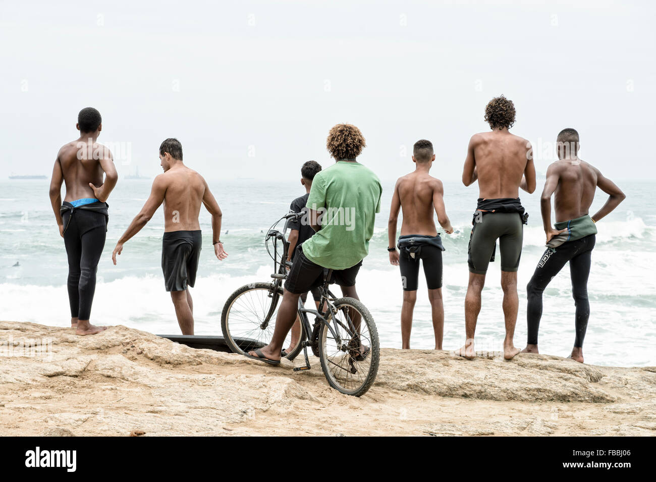 RIO DE JANEIRO, BRAZIL - OCTOBER 22, 2015: Brazilian surfers in wetsuits stand looking at incoming surf waves at - Stock Image