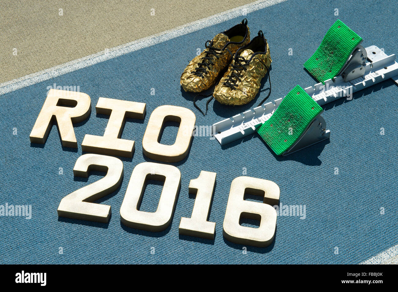NEW YORK CITY, USA - AUGUST 20, 2015: Gold Rio 2016 message shines next to running shoes and starting blocks at - Stock Image