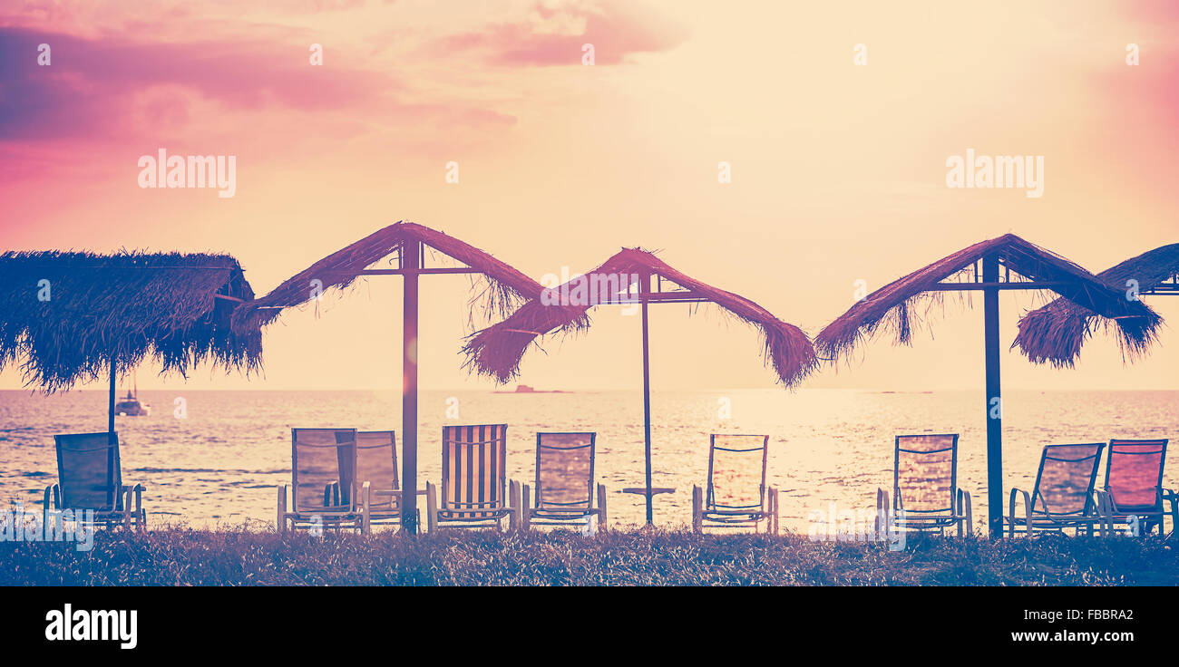 Vintage toned beach chairs and umbrellas at sunset, holidays background. - Stock Image