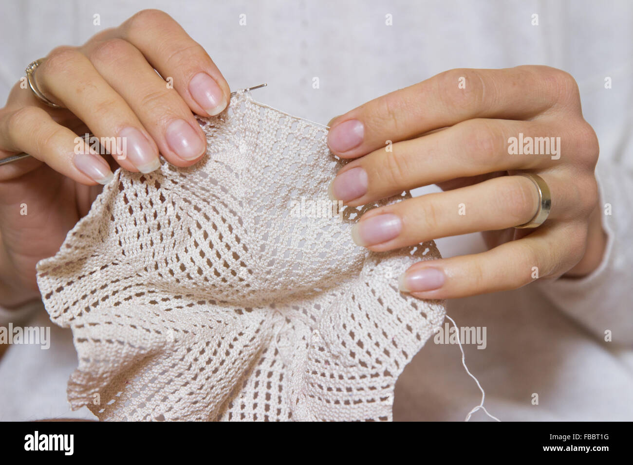 crochet woman crafting making knitting pattern knitted handmade lace detail stitch texture beige yarn openwork hands - Stock Image