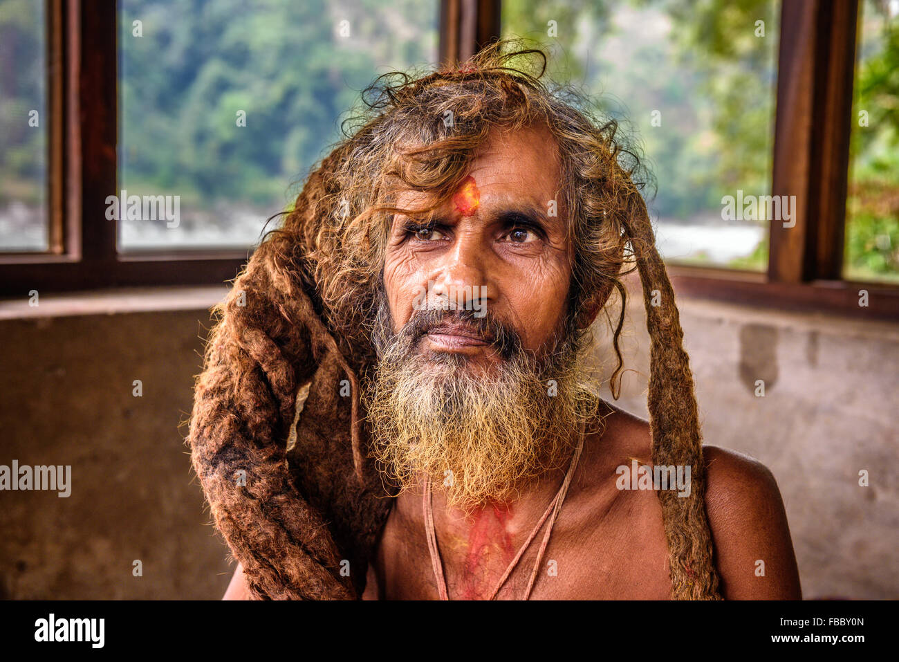 Portrait of a Sadhu baba  (holy man) with traditional long hair in a nepalese temple - Stock Image