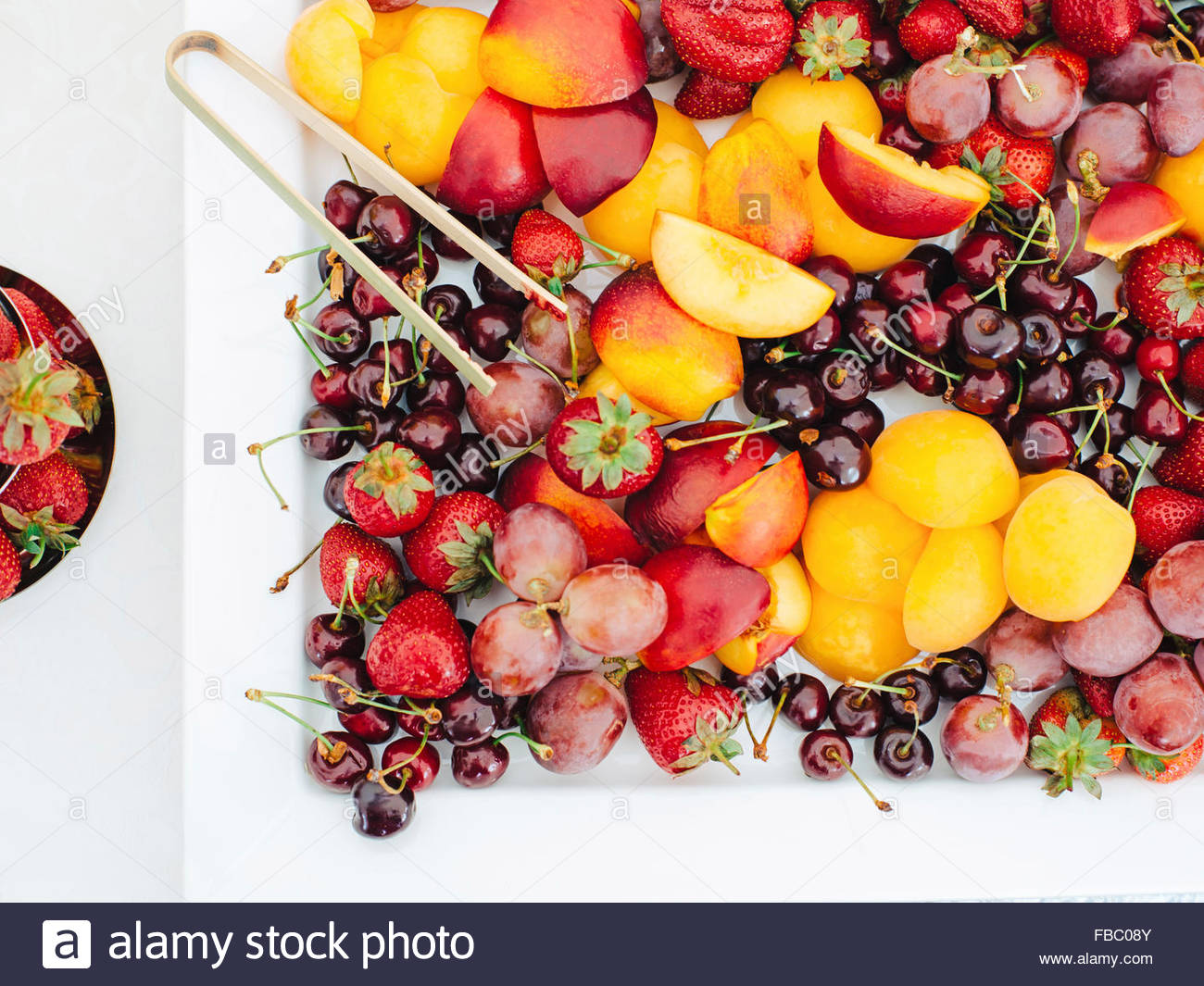 White plate with fruits and berries on table outdoor - Stock Image