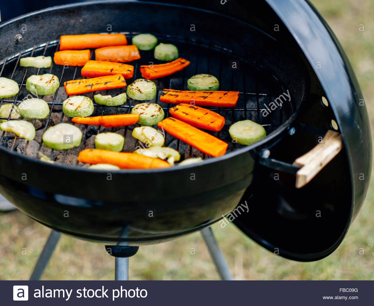 Open grill full of carrots and zucchini - Stock Image