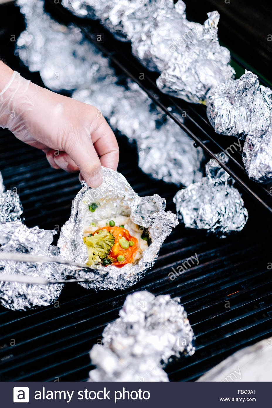 Grill with of vegetables in foil - Stock Image