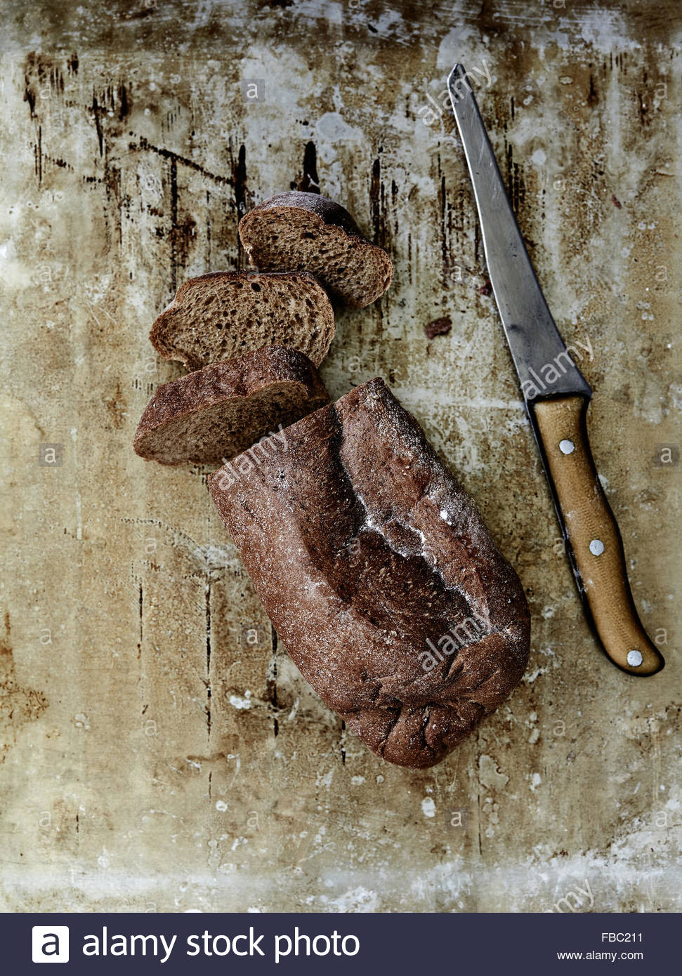 Sliced rye bread and rustic knife on old metal sheet - Stock Image