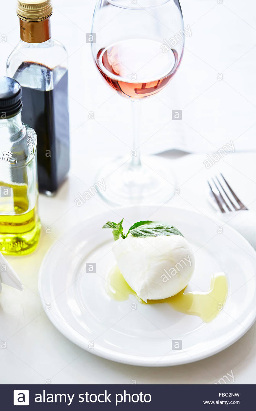 Fresh buffalo mozzarella ball with olive oil, basil and wine on white table - Stock Image