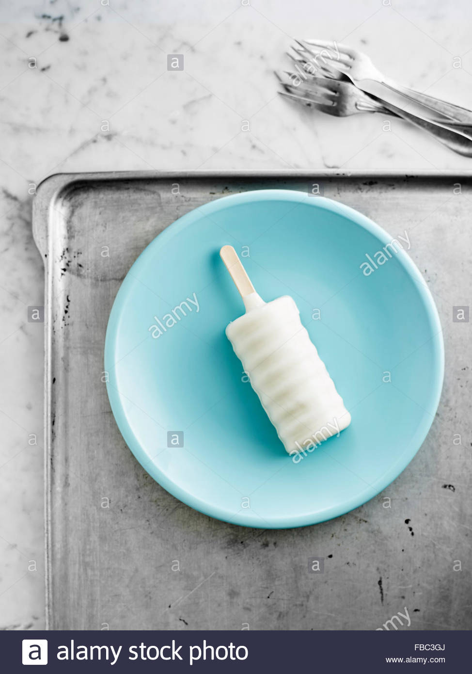 White creamsicle on blue plate - Stock Image
