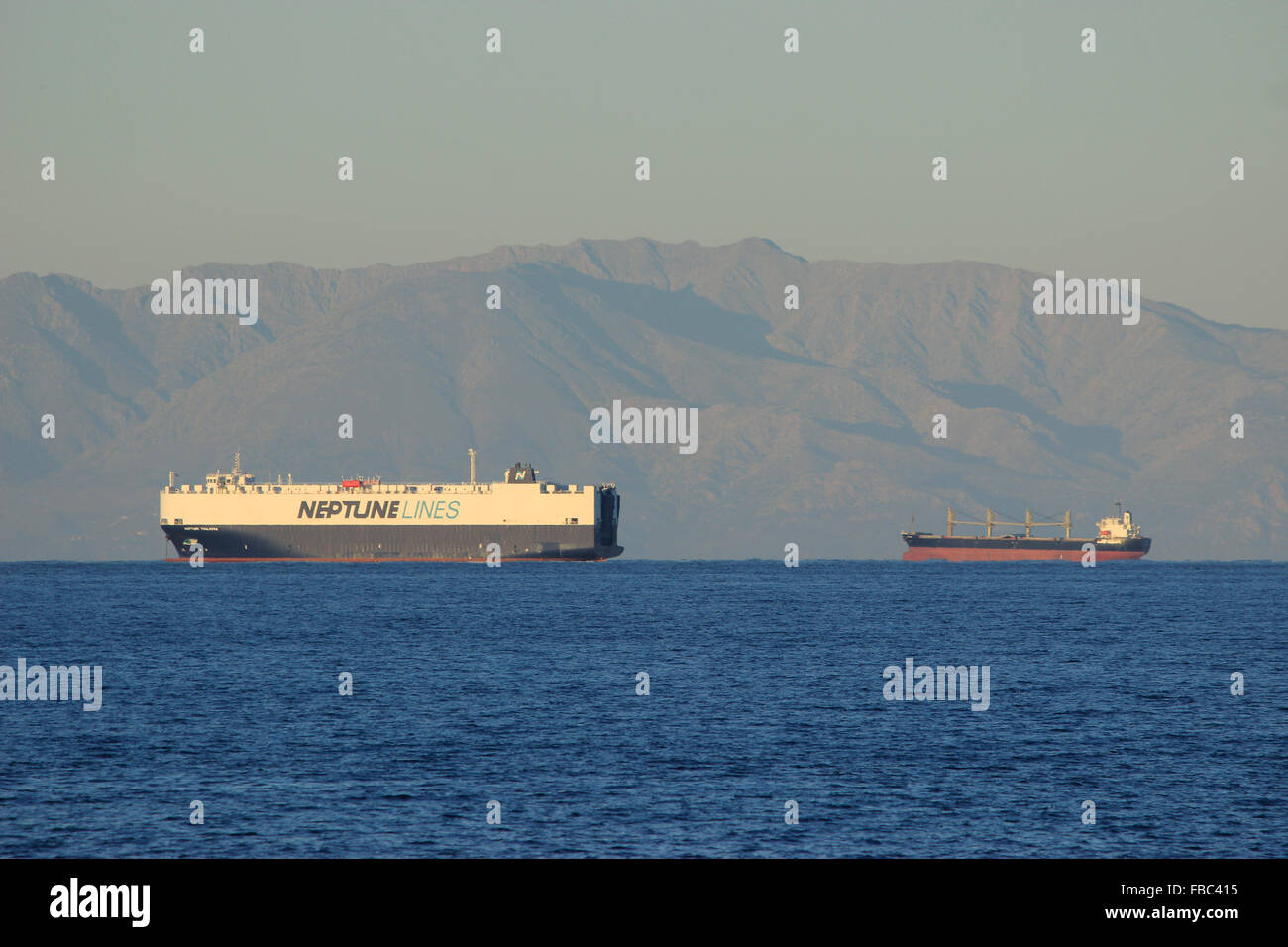 Neptune lines (PCTC) pure car and truck carrier vessel sailing in the aegean sea. Samothrace island in the background. - Stock Image