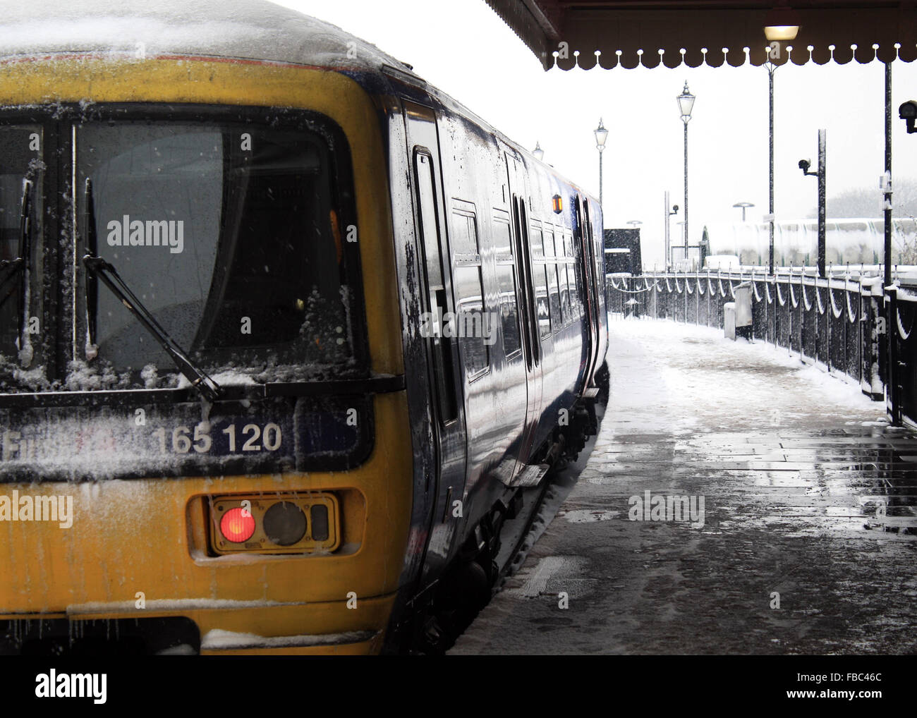 Winter's view of a train at Windsor and Eton railway station, with ice and snow on the train and platform. - Stock Image