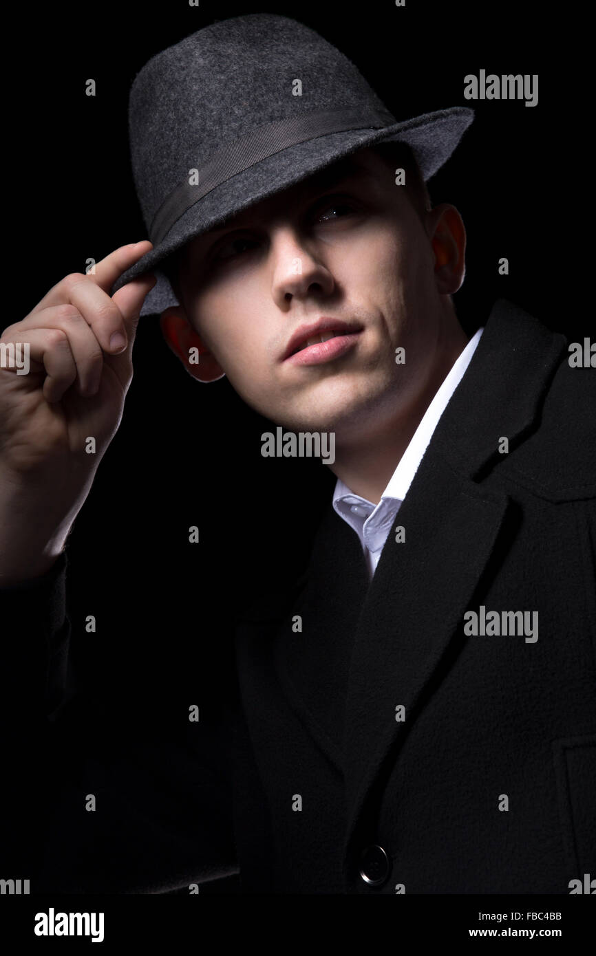 Brutal looking man hiding his eyes in the darkness, touching his hat, greeting, unrecognizable person, low key studio - Stock Image