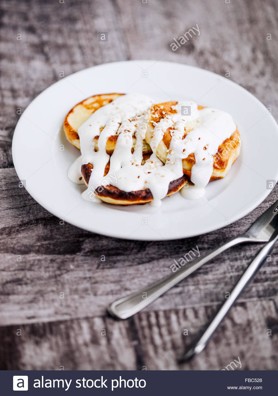 Cheese pancakes with sour cream on rustic table - Stock Image