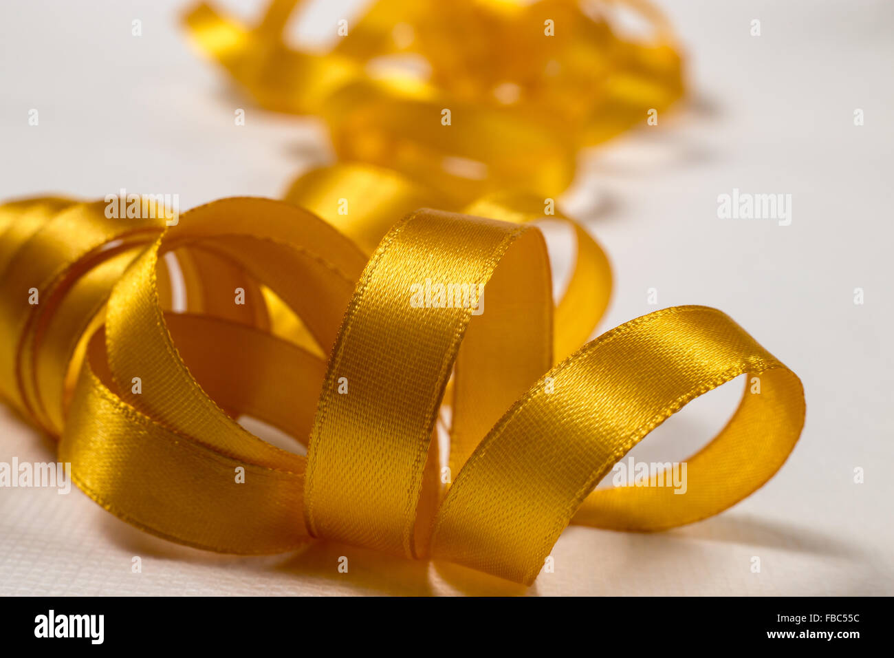 Close-up of golden ribbon unraveling in a mess on white background - Stock Image