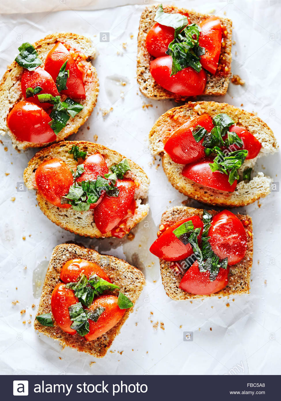 Six bruschettas with tomatoes and herbs on baking paper - Stock Image