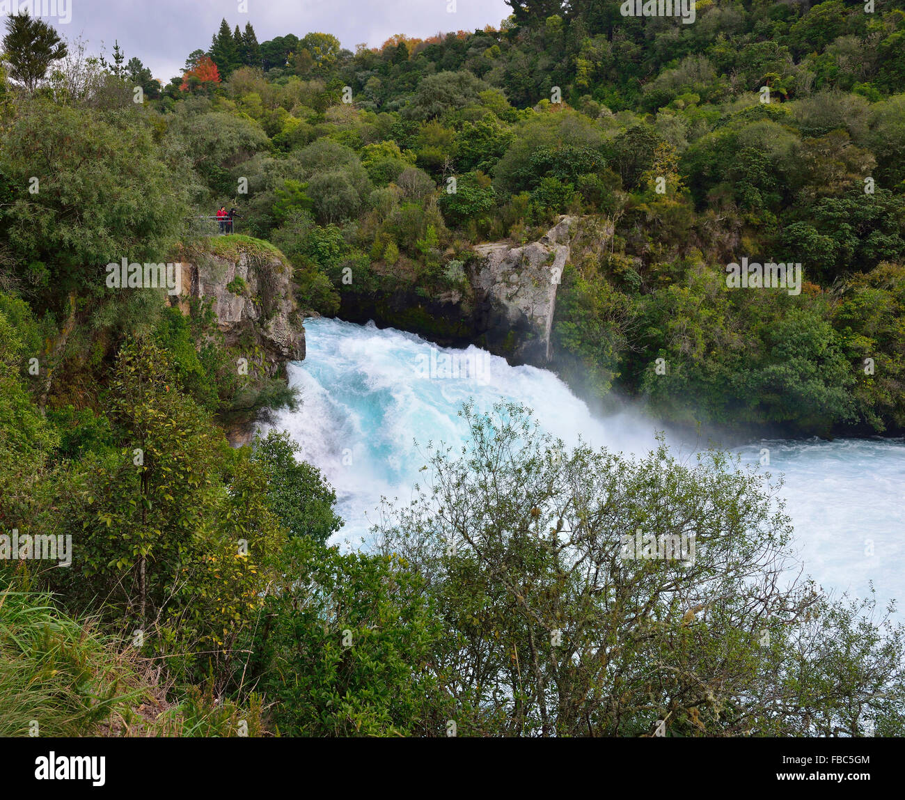 Huka Falls 2 people looking over at the  phenomenon of natural hydro power - more than 220,000 litres of water per - Stock Image