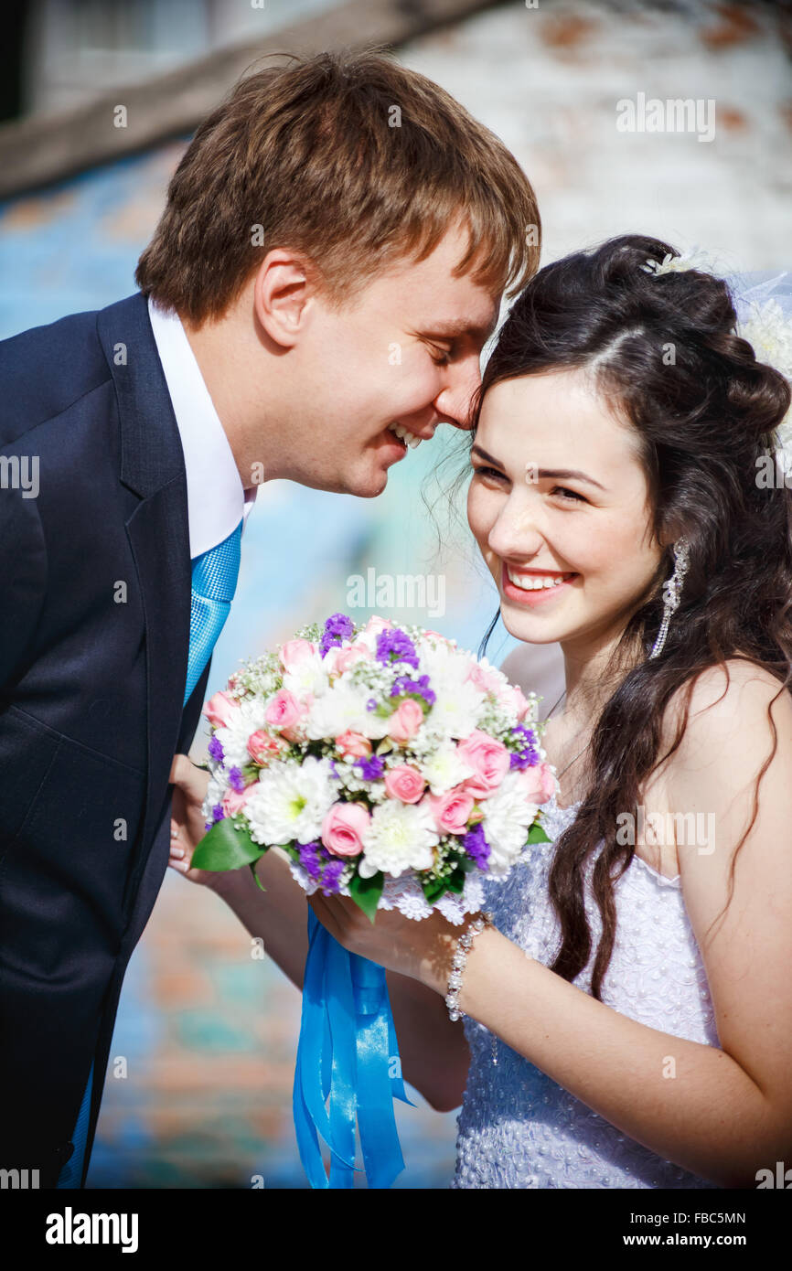 The bride and groom are rolled with laughter, giggle, laugh merrily. Groom in a turquoise tie, he leaned over his - Stock Image