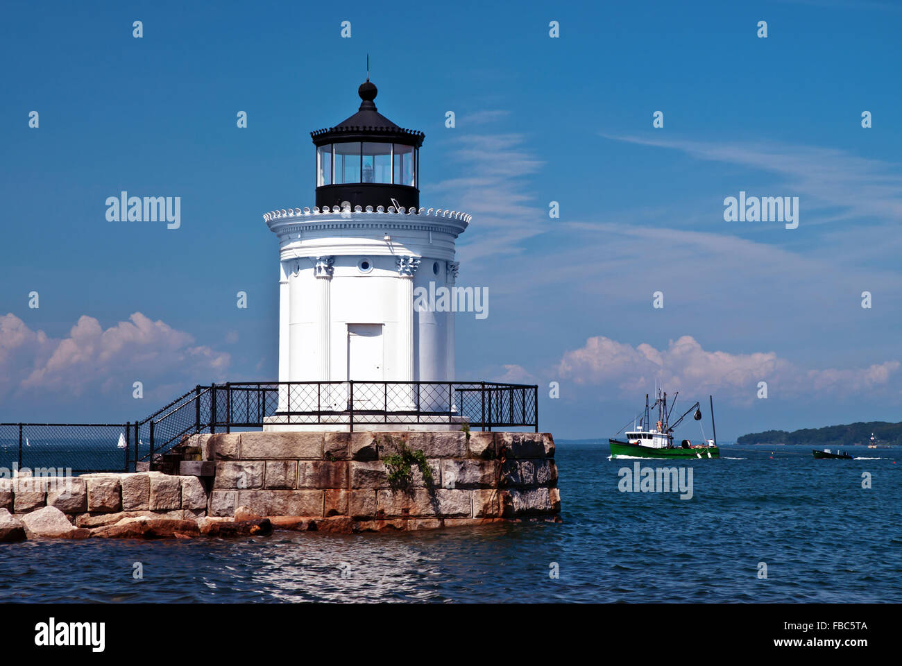 Portland Breakwater lighthouse, also referred to as Bug light, guides a fishing trawler home. It has distinctive - Stock Image