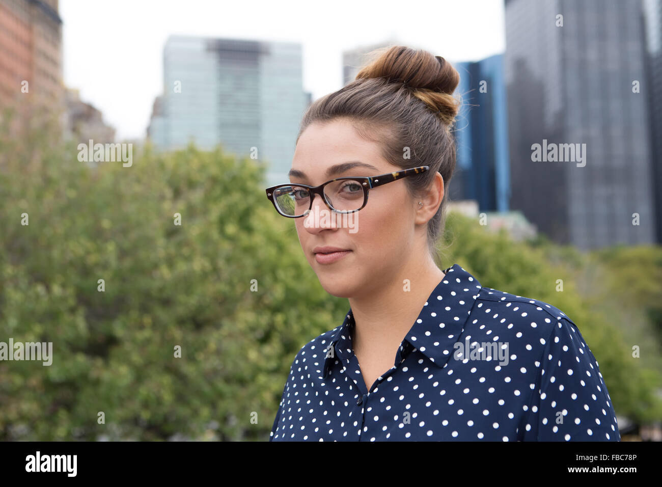 Tight shot of a young professional business woman with high rise building in the background. Photographed in New - Stock Image