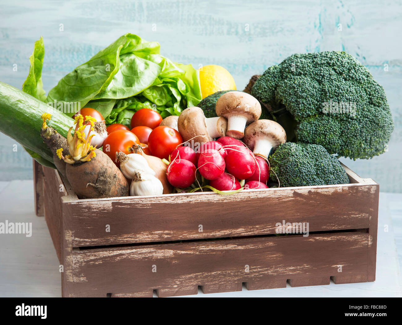 Fresh bio vegetables in wooden crate with salad,carrots,mushrooms,tomatoes,broccoli,radish,avocado,onions and garlic Stock Photo